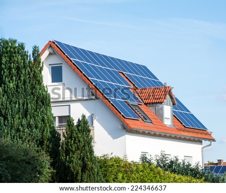 Modern house with photovoltaic solar cells on the roof for alternative energy production - stock photo