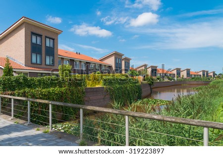 modern houses at a small pond in the netherlands - stock photo