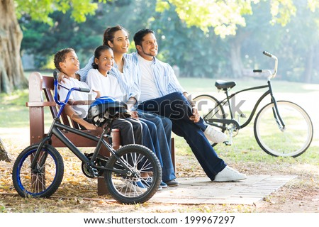modern indian family sitting on bench and relaxing in the park - stock photo