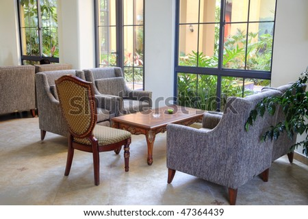Modern interior of a hall with a sofa zone and a small garden outside. - stock photo