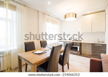 Modern interior of a living room studio. Large spacious kitchen in moderate tone. A large wooden table in the interior - stock photo