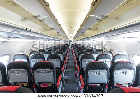 Modern interior of aircraft. Black and red seats inside airplane. Symmetric vanishing row of seats inside air transport. Economy class of flight. Equipment for travelling. Empty illuminated plane. - stock photo
