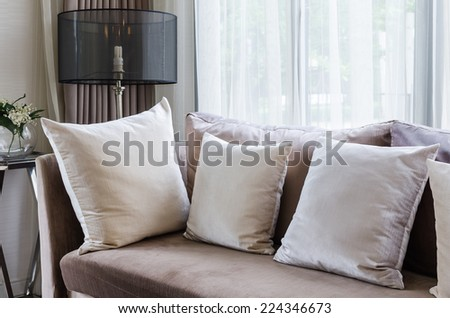 modern interior pillows on brown sofa with lamp - stock photo