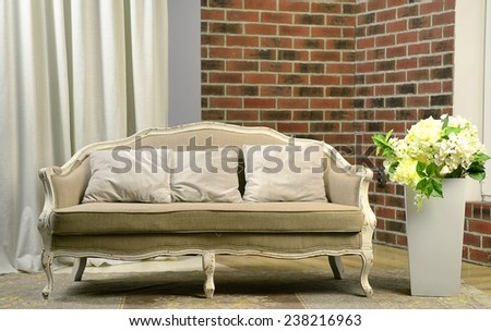 Modern interior room with sofa and flowers in big vase about brick wall - stock photo