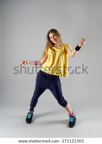 Modern jazz dance workout. Portrait of happy smiling female doing sport in gym class.  - stock photo