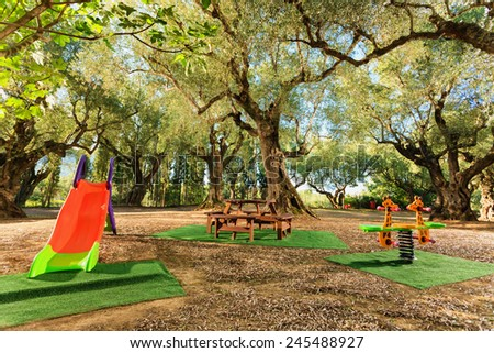 modern kids playground in a beautiful garden with olive trees in a summer beach resort - stock photo