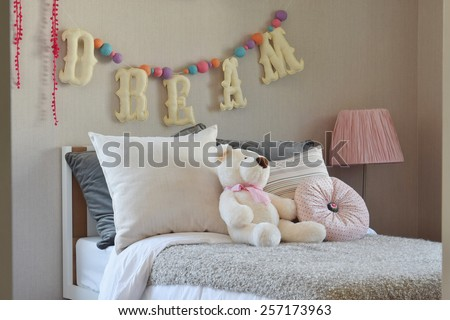 modern kids room with doll and pillows on bed - stock photo