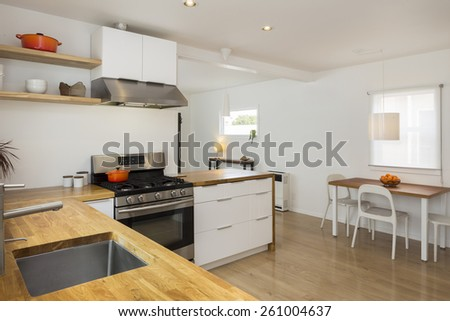 Modern kitchen interior in with white cabinets and amazing wooden counter top and breakfast table. Amazing Design concept. - stock photo
