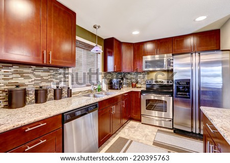 Modern kitchen interior with bright wooden cabinets and steel appliances. Mosaic back splash trim blend perfectly with granite tops - stock photo