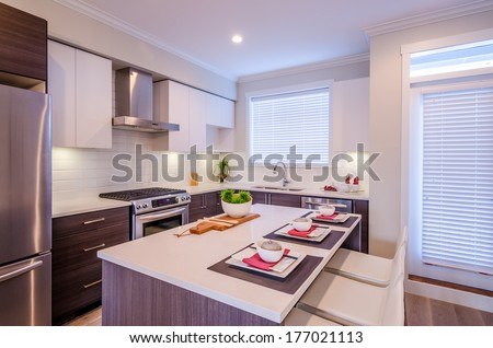 Modern kitchen interior with island and cabinets in a luxury house - stock photo