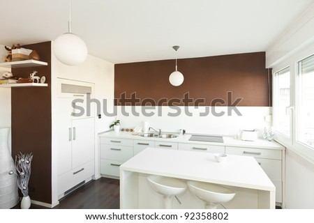 Modern kitchen with brown wall above the counter with white furniture - stock photo