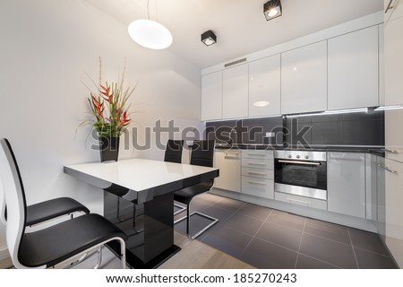 Modern kitchen with gray tile floor and white table - stock photo