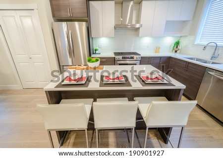 Modern kitchen with island and cabinets in a luxury house set for dinner. Interior design. - stock photo