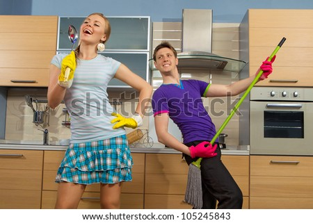 Modern kitchen - woman pretend to sing song with ladle and smiling young man cleaning the floor at home and play like guitar with  mop - stock photo