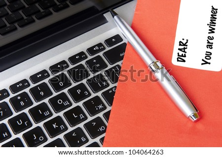 modern laptop and post envelope YOU ARE WINNER with pen - stock photo
