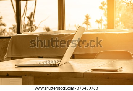 modern laptop on wood table with sunlight - stock photo