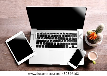 Modern laptop, smart phone and tablet with coffee cup on a wooden table - stock photo