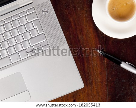 Modern laptop with a cup of coffee next to it - stock photo