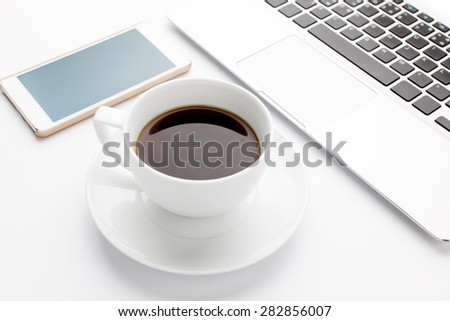 Modern laptop with mobile phone and cup of coffee - stock photo