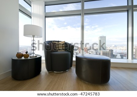 Modern leather armchair with taboret and side table with stylish lamp - stock photo