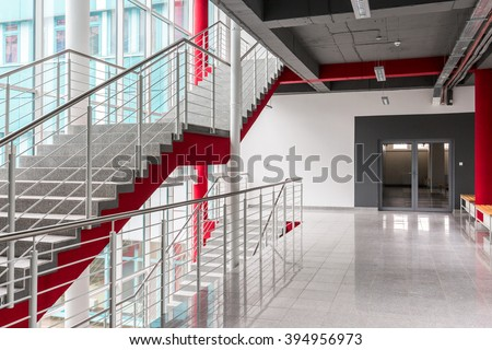 Modern, light staircase with silver railing, red details and black ceiling - stock photo