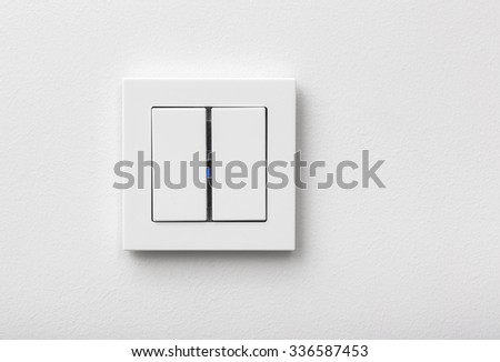 Modern light switch in the frame on white wall - stock photo