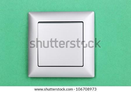 Modern light switch on green background - stock photo