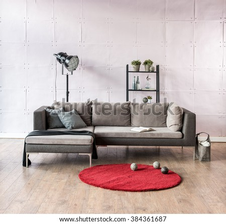 modern living room corner sofa behind stone soft wall and black lamp with red carpet  - stock photo