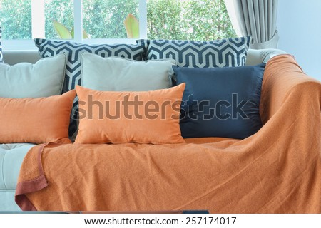 modern living room design with brown and orange tweed sofa and black pillows - stock photo