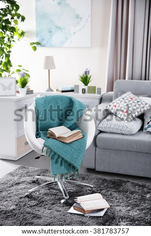 Modern living room interior in grey tones with bright blue plaid and book on chair - stock photo