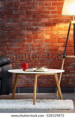 Modern living room interior with armchair, table and lamp - stock photo