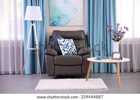 Modern living room interior with coffee table, armchair and stand - stock photo