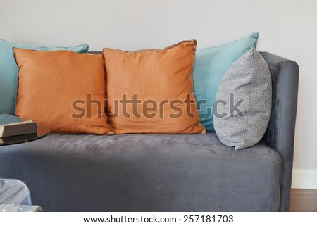 modern living room interior with grey velvet sofa and colorful pillows at home - stock photo
