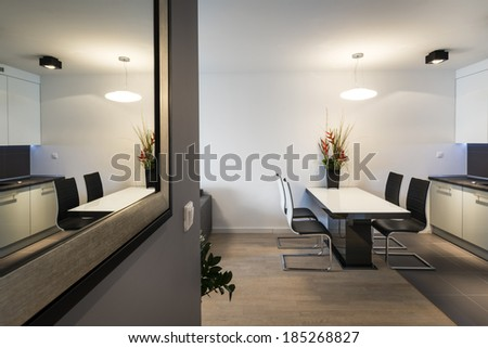 Modern living room interior with kitchen and mirror - stock photo