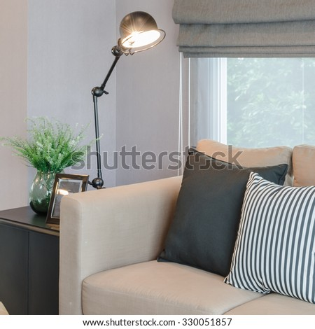 modern living room with black lamp on table side and glass vase of plant - stock photo