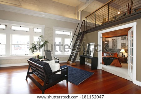 Modern living room with brick painted wall, hardwood floor and iron steep stairs. View of bedroom - stock photo