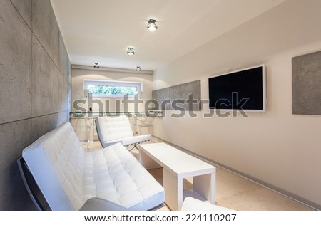 Modern living room with TV on the wall - stock photo