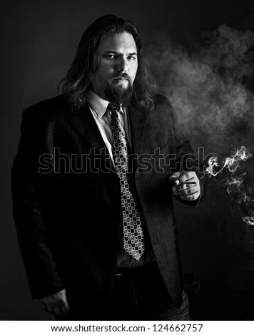 modern looking white man with long hair wearing a sport coat and tie smoking a cigarette. - stock photo
