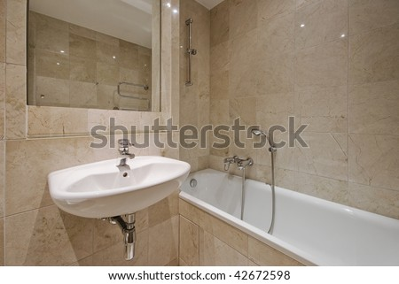 modern luxury bathroom with beige marble tiles and white ceramic suite - stock photo