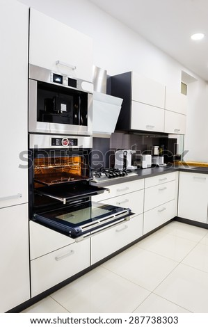 Modern luxury hi-tek black and white kitchen, clean interior design, focu at oven with door open - stock photo