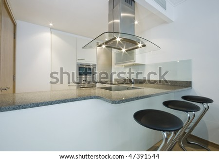 modern luxury kitchen with breakfast bar and built-in appliances - stock photo