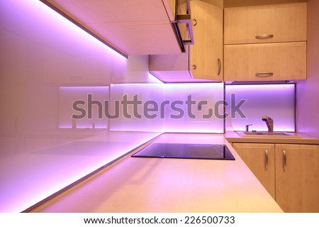 Modern luxury kitchen with pink LED lighting - stock photo
