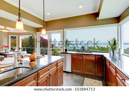 Modern luxury kitchen with water view, island and sink. - stock photo