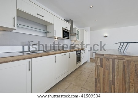 modern luxury penthouse kitchen with separate serving table and breakfast bar - stock photo