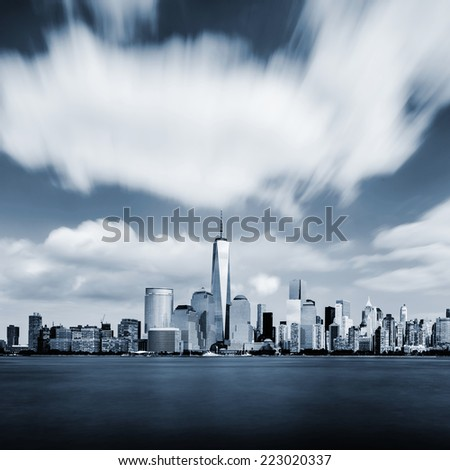 Modern Manhattan cityscape in blue color with blurred sky - stock photo