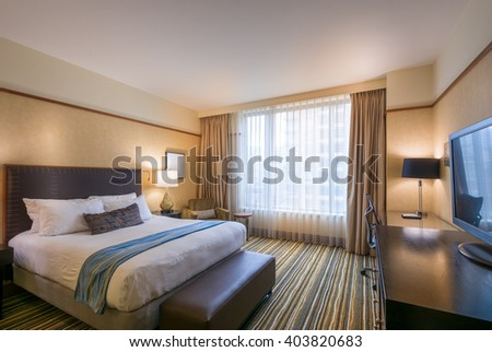 Modern master bedroom in a luxury house, hotel with a bright office and a large window. - stock photo