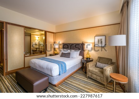 Modern master bedroom in a luxury house, hotel with a window into a bathroom. Interior design. - stock photo