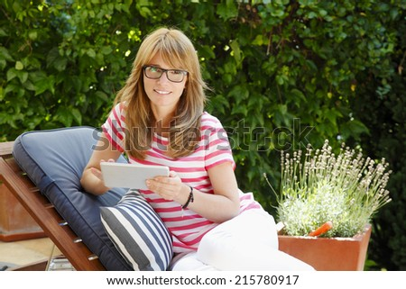 Modern mature woman sitting at garden, while working at home. Small business,  - stock photo