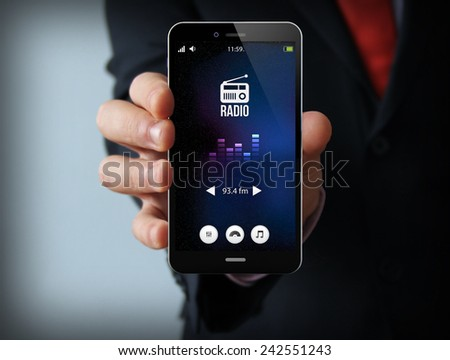 modern media concept: businessman holding a modern smartphone with radio app - stock photo