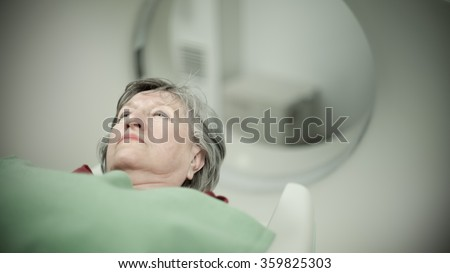 Modern medical equipment, preventional medicine and healthcare.Computer tomography scan.Old woman patient at computerized axial tomography (CAT) scan.Examining cancer patient with CT.Tumor detection - stock photo